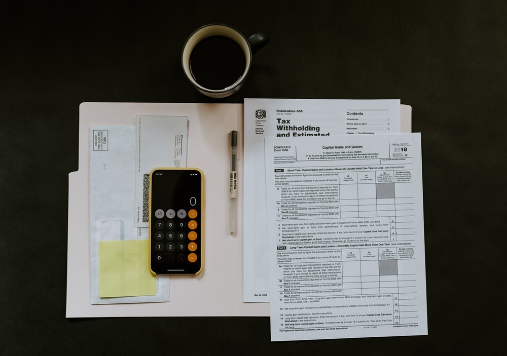 A black phone and ball pen placed over tax documents near a cup of back coffee